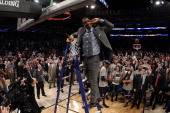 Head coach Kevin Ollie of the Connecticut Huskies cuts down the net after defeating the Michigan State Spartans to win the East Regional Final of the...