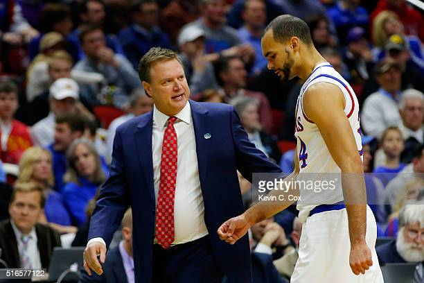 Head coach Kevin Ollie talks to Perry Ellis of the Kansas Jayhawks as he walks off of the court after injuring his knee in the first half against the...