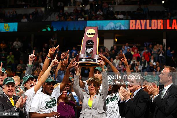 Head coach Kim Mulkey of the Baylor Bears holds up the National Championship trophy as she celebrates with her players after they won 8061 against...