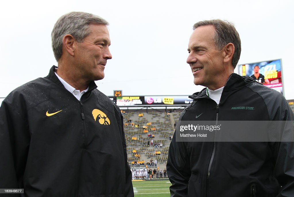 Head coach Kirk Ferentz of the Iowa Hawkeyes visits with head coach Mark Dantonio of the Michigan State Spartans before their match-up on October 5, 2013 at Kinnick Stadium in Iowa City, Iowa. Michigan State won 26-14.