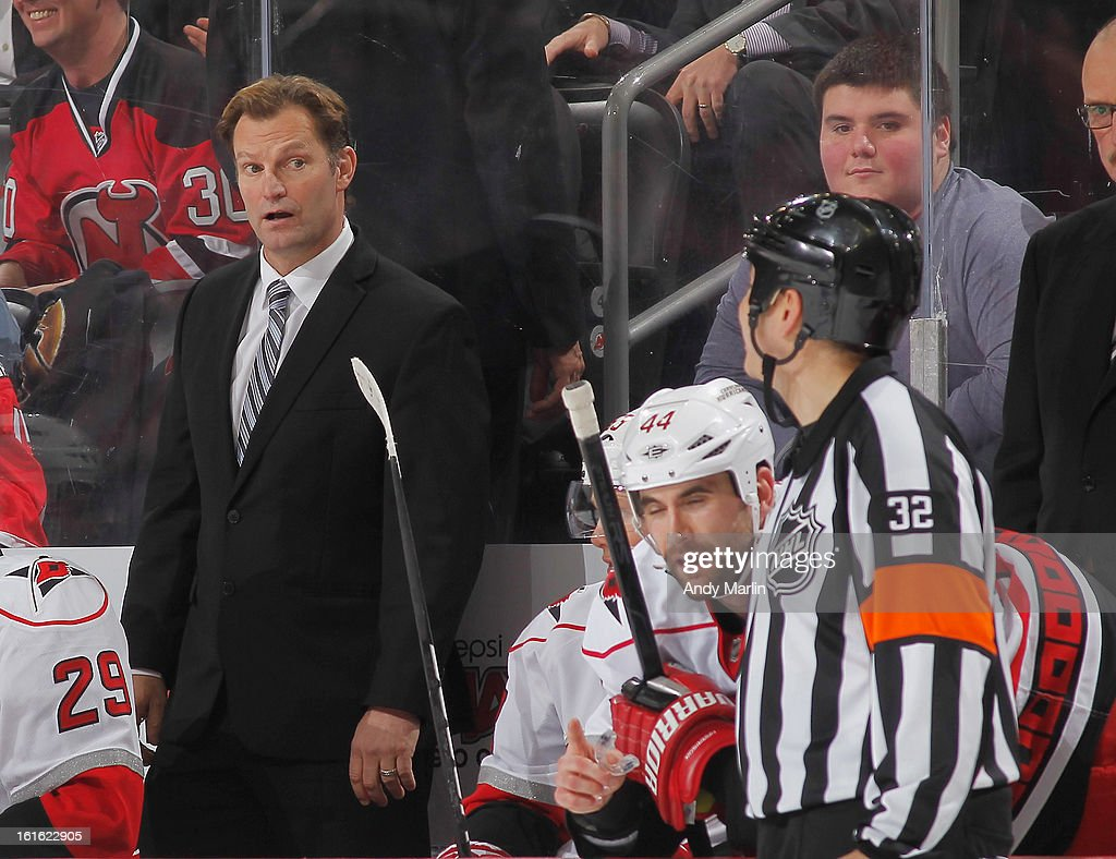 Head coach Kirk Muller of the Carolina Hurricanes chats with referee Tom Kowal during a timeout against the New Jersey Devils during the game at the Prudential Center on February 12, 2013 in Newark, New Jersey.