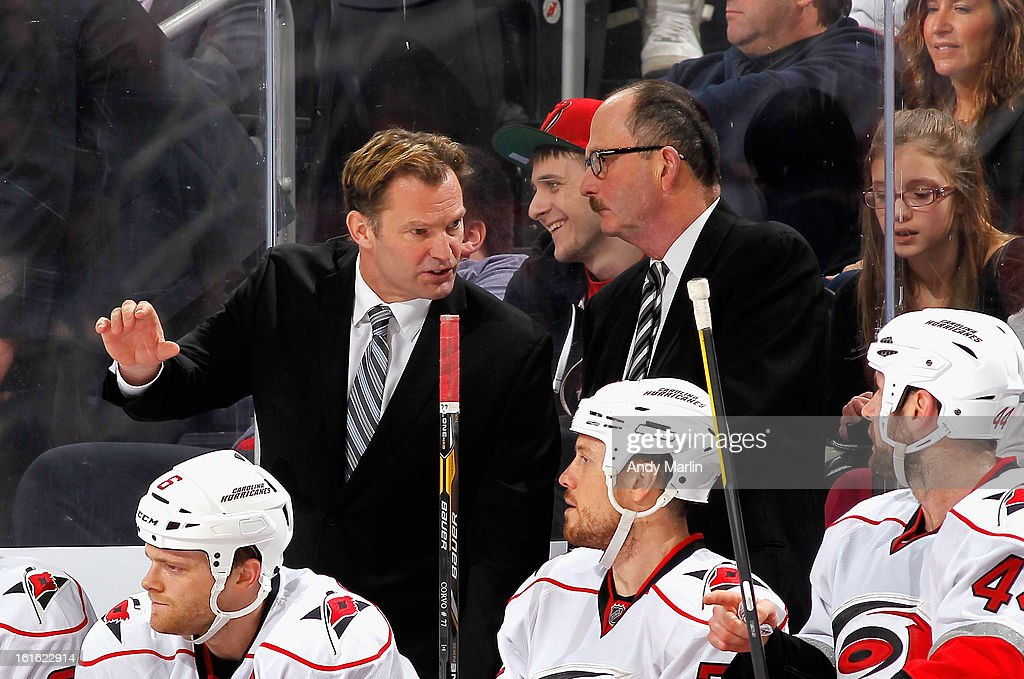 Head coach Kirk Muller (L) of the Carolina Hurricanes gives instructions as assistant coach Dave Lewis looks on against the New Jersey Devils during the game at the Prudential Center on February 12, 2013 in Newark, New Jersey.