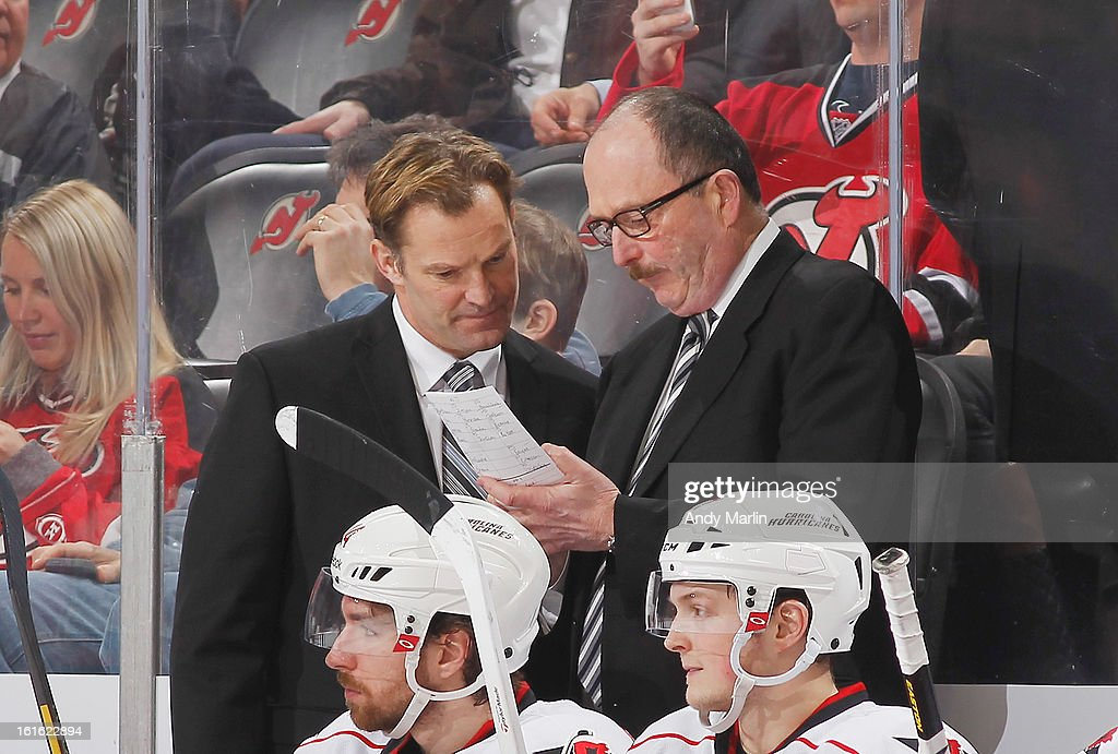 Head coach Kirk Muller (L) of the Carolina Hurricanes has a discussion with assistant coach Dave Lewis against the New Jersey Devils during the game at the Prudential Center on February 12, 2013 in Newark, New Jersey.