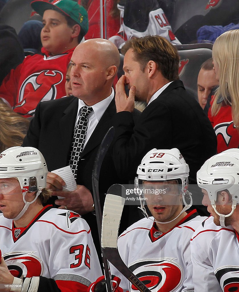 Head coach Kirk Muller (R) of the Carolina Hurricanes has a discussion with assistant coach John MacLean against the New Jersey Devils during the game at the Prudential Center on February 12, 2013 in Newark, New Jersey.