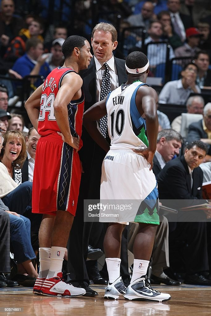 Head coach Kurt Rambis and Jonny Flynn of the Minnesota Timberwolves talk with Devin Harris of the New Jersey Nets during the season opening game on...