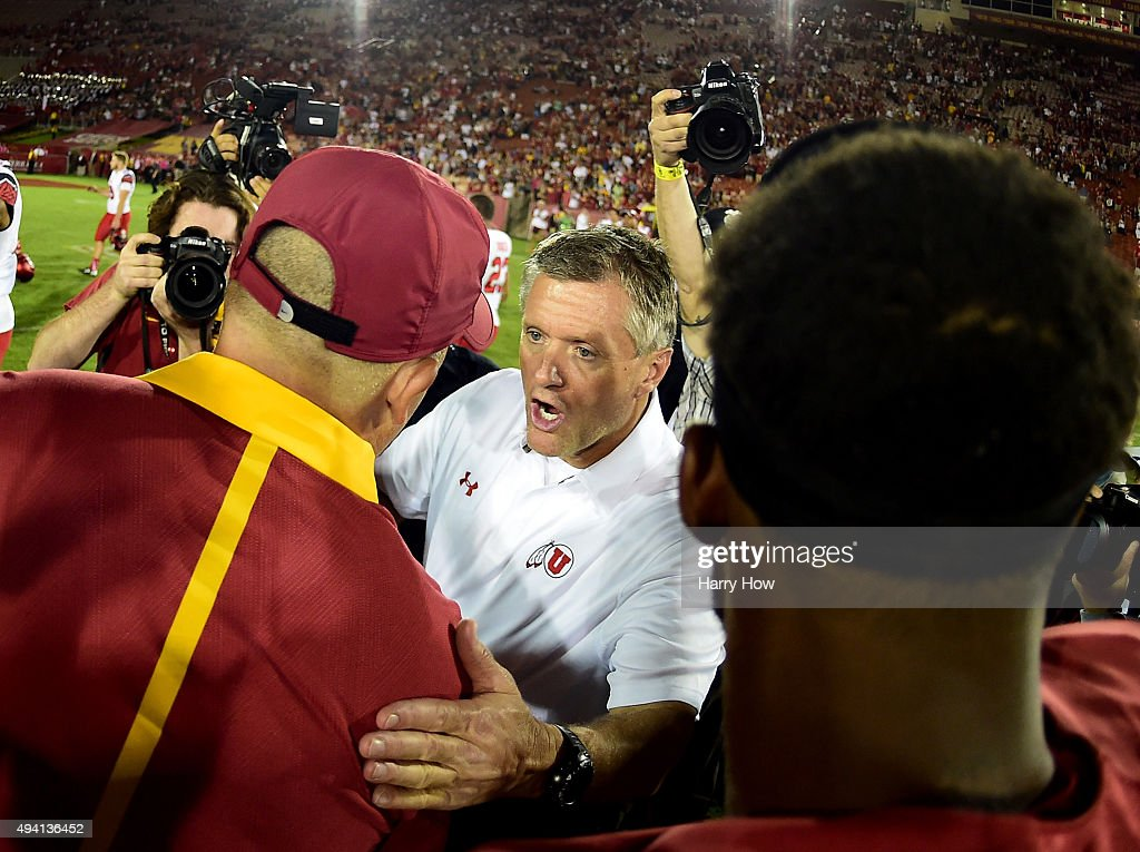 Head coach Kyle Whittingham of the Utah Utes congratulates head coach Clay Helton of the USC Trojans on a 42-24 win at Los Angeles Memorial Coliseum on October 24, 2015 in Los Angeles, California.
