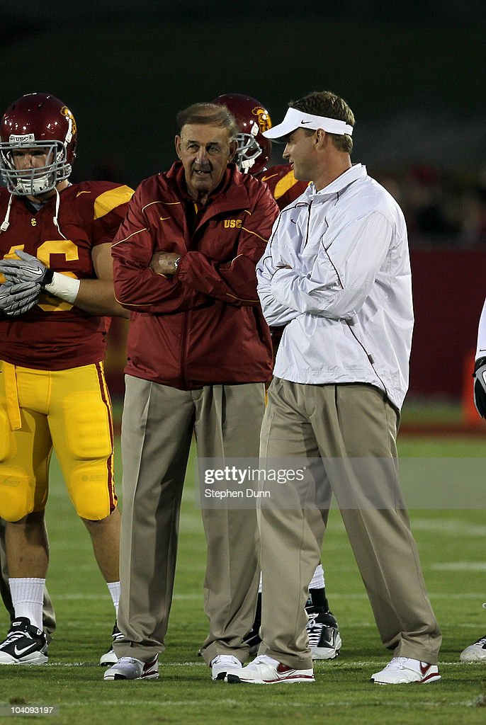 Head coach Lane Kiffin and his father and defensive coordinator Monte Kiffin of the USC Trojans talk during warmups for their game with the Virginia...