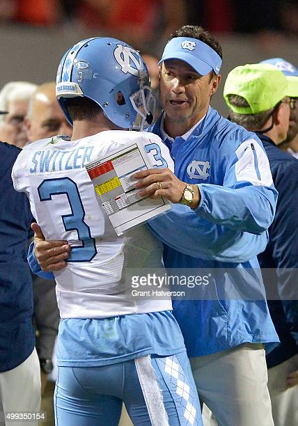 Head coach Larry Fedora hugs Ryan Switzer of the North Carolina Tar Heels during their win against the North Carolina State Wolfpack at CarterFinley...