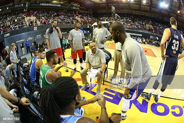Head Coach Lionel Hollins of Team World goes over the game plan with Chris Paul against Team Africa during the NBA Africa Game 2015 as part of...