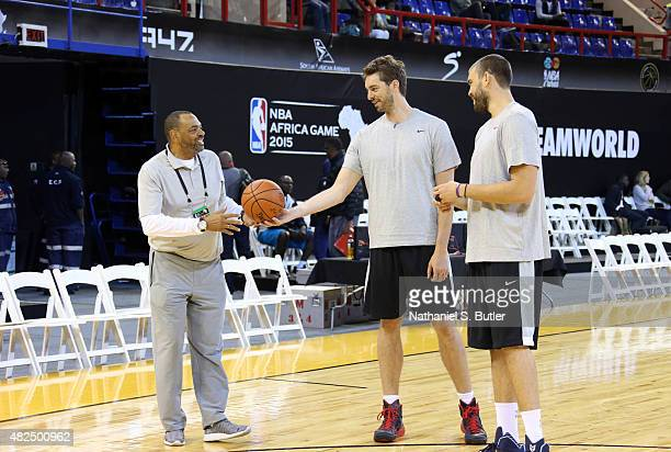 Head Coach Lionel Hollins of Team World smiles with brothers Pau Gasol and Marc Gasol of Team World during practice for the NBA Africa Game 2015 as...