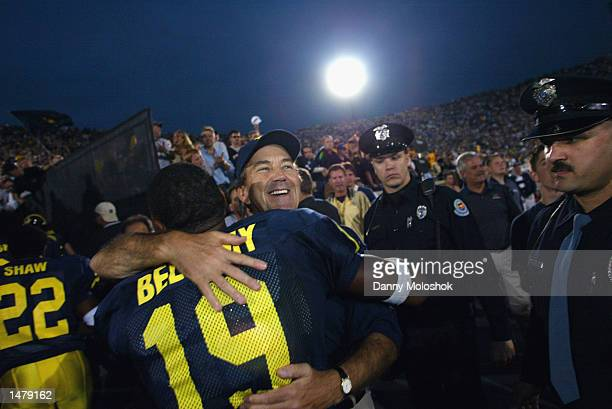 Head Coach Lloyd Carr of the Michigan Wolverines celebrates with Ronald Bellamy after runningback Chris Perry scored in overtime against the Penn...