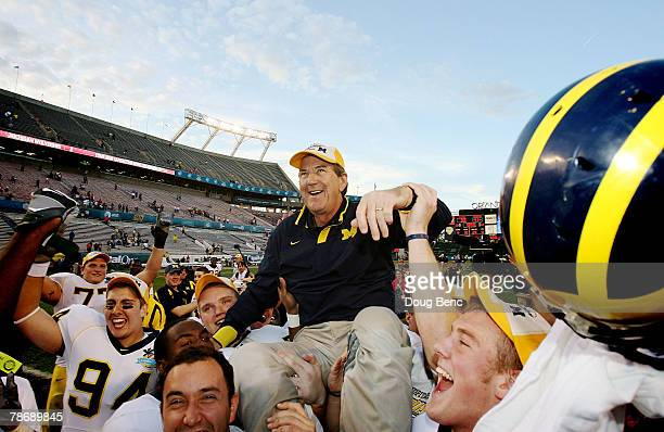 Head coach Lloyd Carr of the Michigan Wolverines is carried off the field after ending his coaching career with a victory over the Florida Gators in...