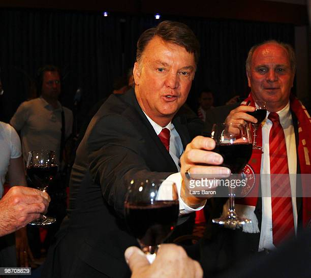 Head coach Louis van Gaal of Muenchen drinks a glass of red vine next to president Uli Hoeness at the Champions League dinner after reaching the...