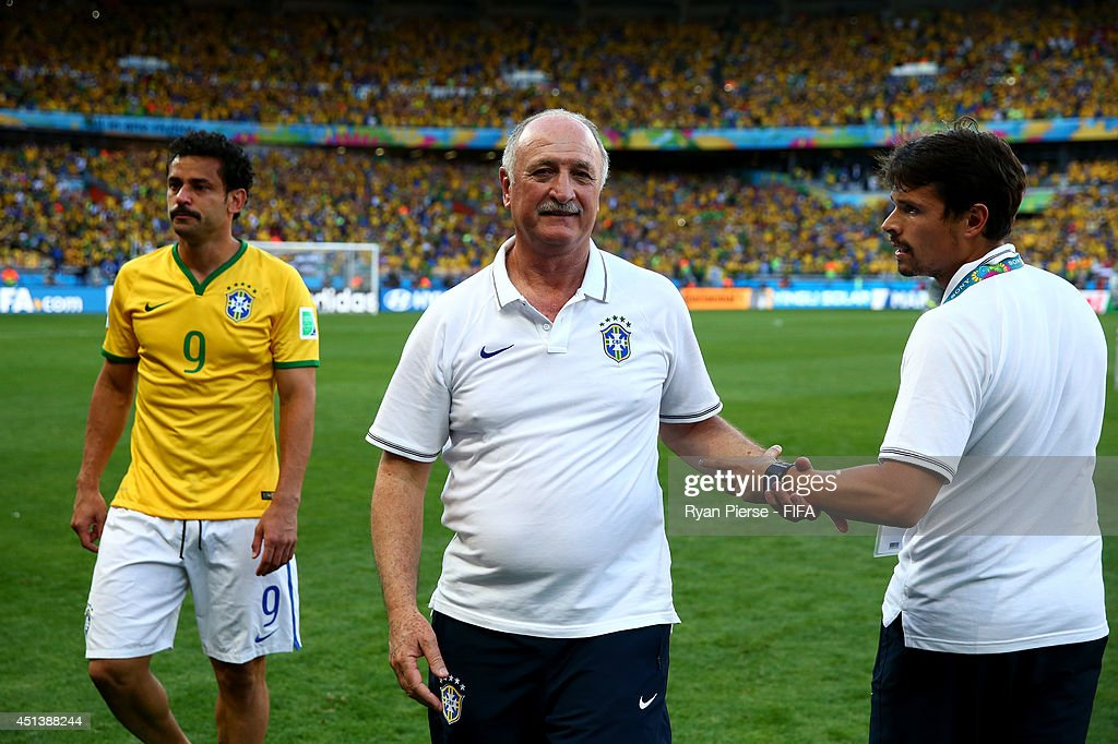 Head coach Luiz Felipe Scolari (C) and Fred (L) of Brazil celebrate the win after the 2014 FIFA World Cup Brazil Round of 16 match between Brazil and Chile at Estadio Mineirao on June 28, 2014 in Belo Horizonte, Brazil.