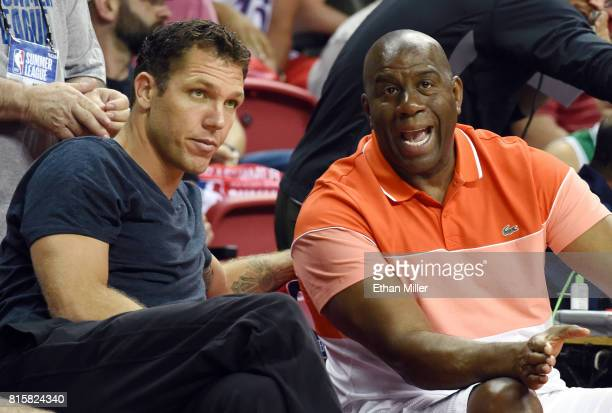Head coach Luke Walton of the Los Angeles Lakers and Lakers president of basketball operations Earvin 'Magic' Johnson talk courtside during the...