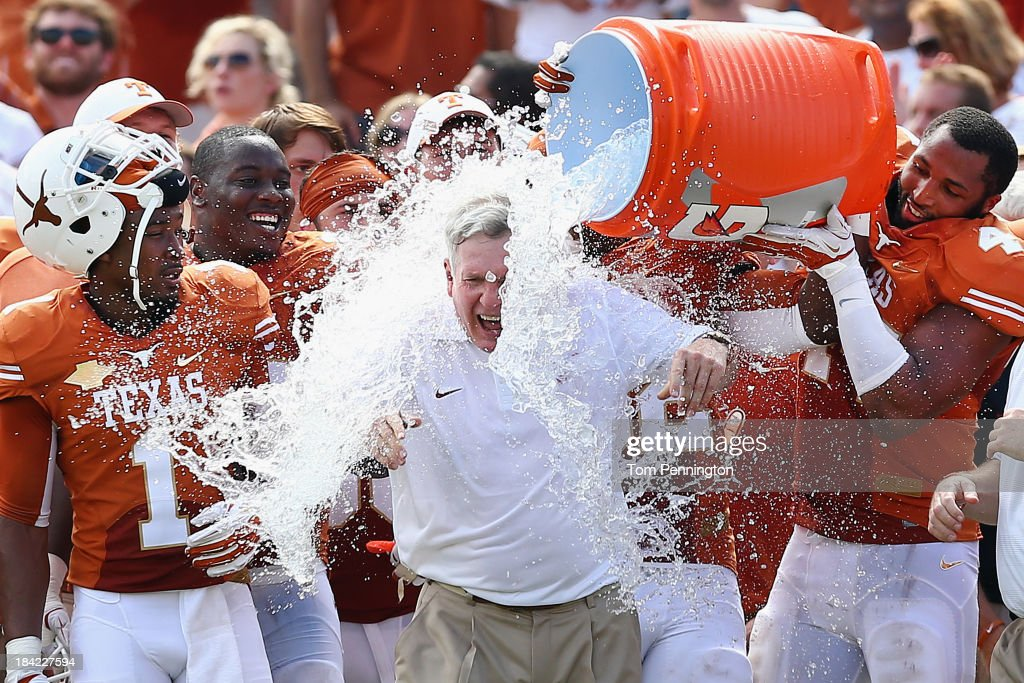 Head coach Mack Brown of the Texas Longhorns has a cooler of ice water dumped on him by his team after the Longhorns beat the Oklahoma Sooners 36-20 at the Cotton Bowl on October 12, 2013 in Dallas, Texas.