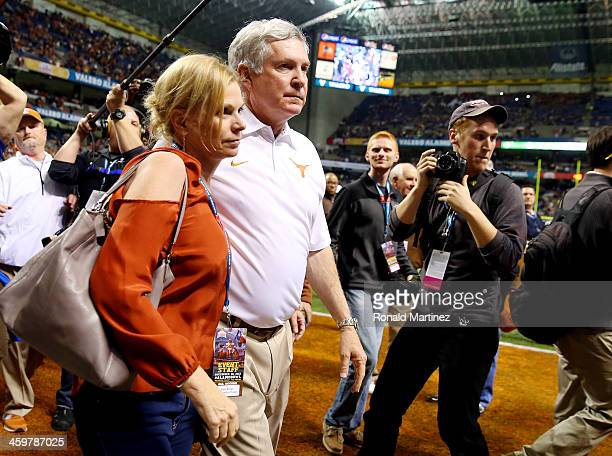 Head coach Mack Brown of the Texas Longhorns walks off the field with his wife Sally after losing to the Oregon Ducks 307 in the Valero Alamo Bowl at...