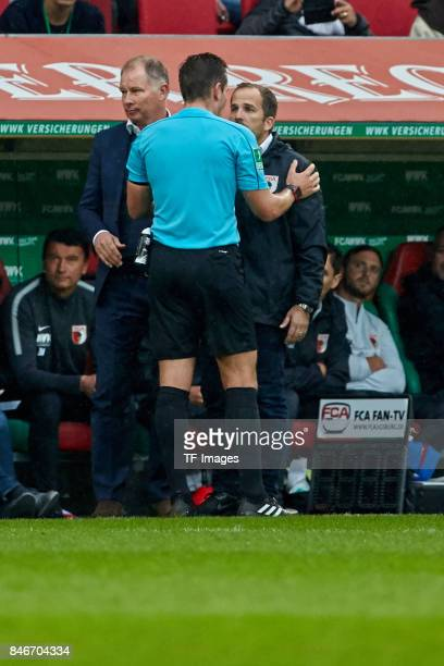 Head coach Manuel Baum of Augsburg speak with referee Tobias Stieler during the Bundesliga match between FC Augsburg and 1 FC Koeln at WWKArena on...