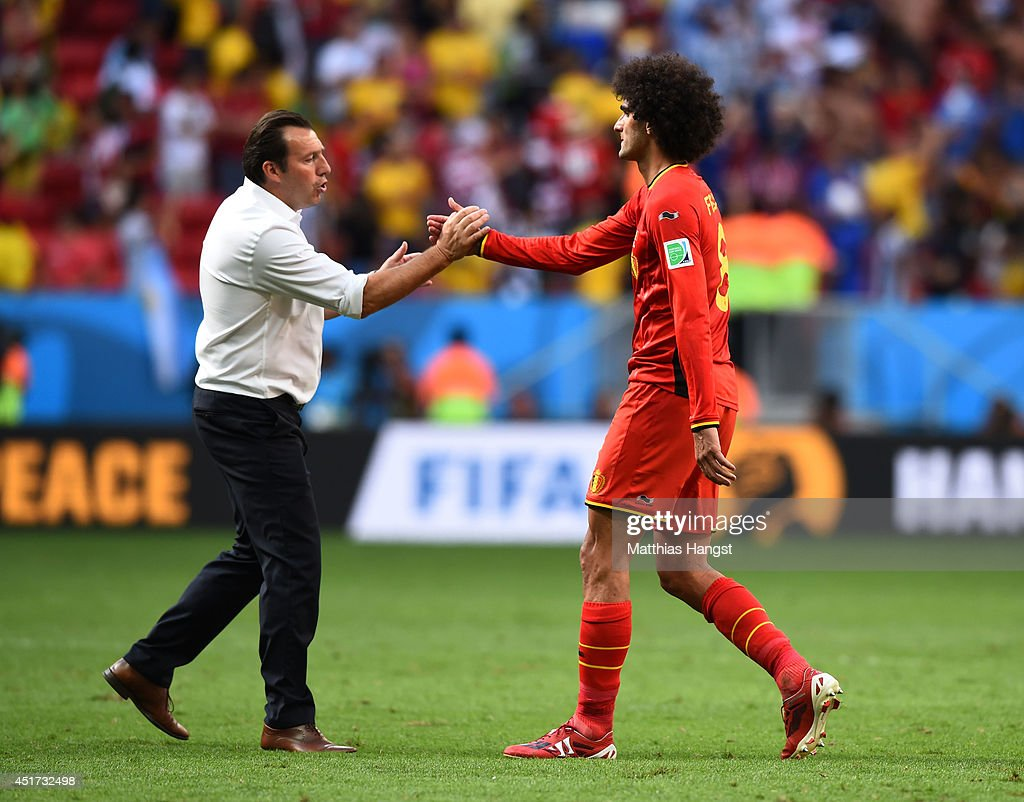 Head coach <a gi-track='captionPersonalityLinkClicked' href=/galleries/search?phrase=Marc+Wilmots&family=editorial&specificpeople=1016207 ng-click='$event.stopPropagation()'>Marc Wilmots</a> and <a gi-track='captionPersonalityLinkClicked' href=/galleries/search?phrase=Marouane+Fellaini&family=editorial&specificpeople=3936316 ng-click='$event.stopPropagation()'>Marouane Fellaini</a> of Belgium shake hands after a 1-0 defeat to Argentina in the 2014 FIFA World Cup Brazil Quarter Final match between Argentina and Belgium at Estadio Nacional on July 5, 2014 in Brasilia, Brazil.