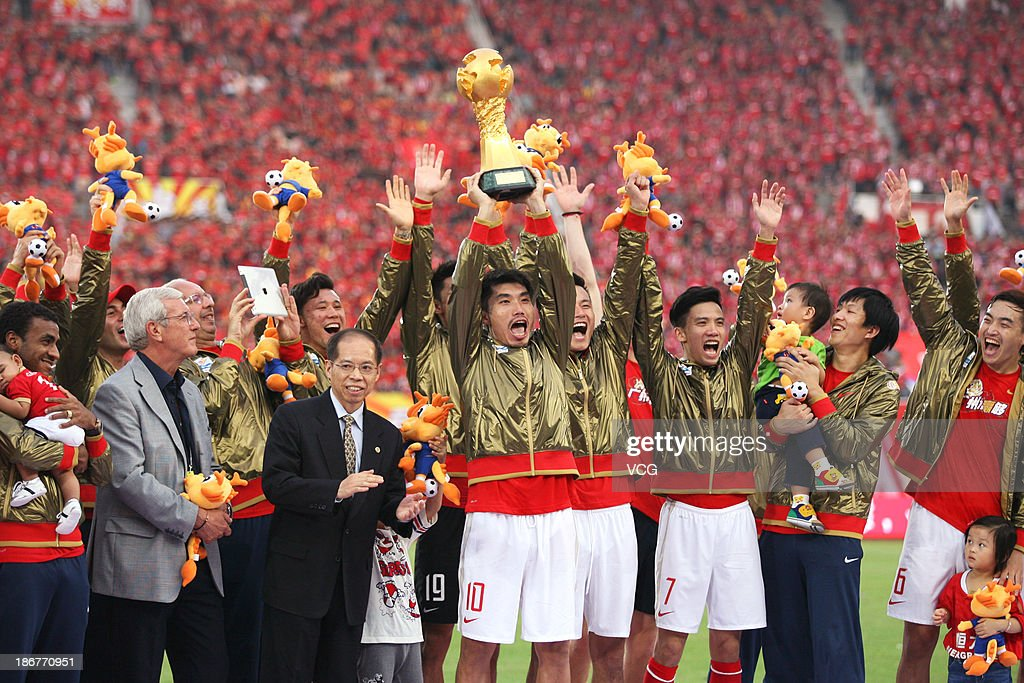 Head coach Marcello Lippi and Guangzhou Evergrande players celebrate with the trophy after defeating Wuhan Zall to win the 2013 Chinese Super League title at Tianhe Sports Center on November 3, 2013 in Guangzhou, China.