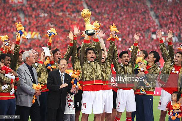 Head coach Marcello Lippi and Guangzhou Evergrande players celebrate with the trophy after defeating Wuhan Zall to win the 2013 Chinese Super League...