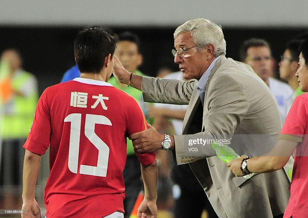 Head coach Marcello Lippi talks to Dario Conca of Guangzhou Evergrande during the Chinese Super League match between Guangzhou Evergrande and...