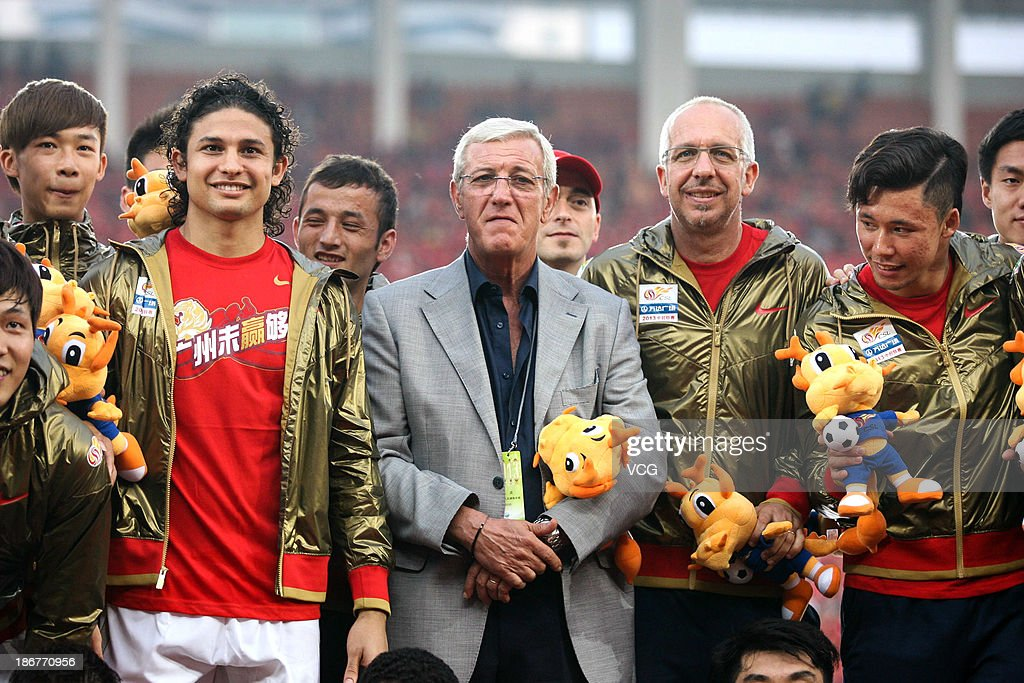 Head coach Marcello Lippi (C), Zhang Linpeng (R) and Elkeson (L) of Guangzhou Evergrande celebrate after defeating Wuhan Zall to win the 2013 Chinese Super League title at Tianhe Sports Center on November 3, 2013 in Guangzhou, China.