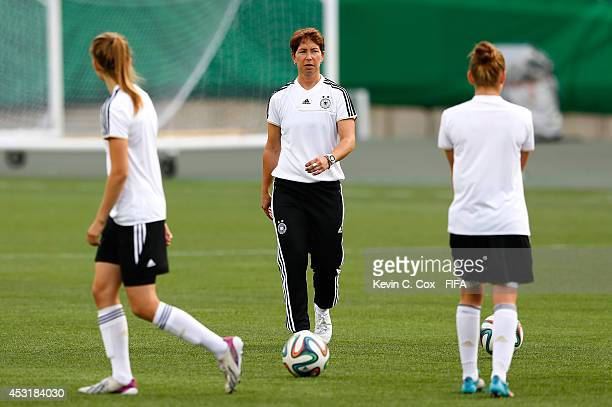 Head coach Maren Meinert of Germany converses with her players during training on August 4 2014 at Commonwealth Stadium in Edmonton Alberta Canada