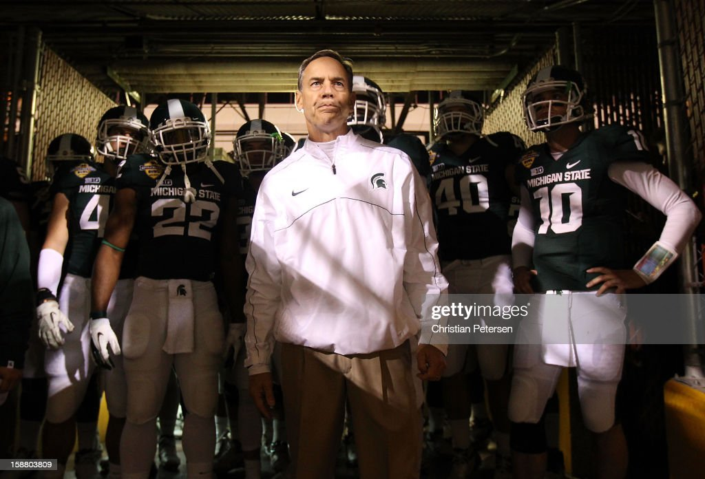 Head coach Mark Dantonio of the Michigan State Spartans stands with his team before taking the field for the Buffalo Wild Wings Bowl against the TCU Horned Frogs at Sun Devil Stadium on December 29, 2012 in Tempe, Arizona.