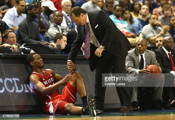 Head coach Mark Gottfried of the North Carolina State Wolfpack helps up his player TJ Warren against the Duke Blue Devils during the semifinals of...
