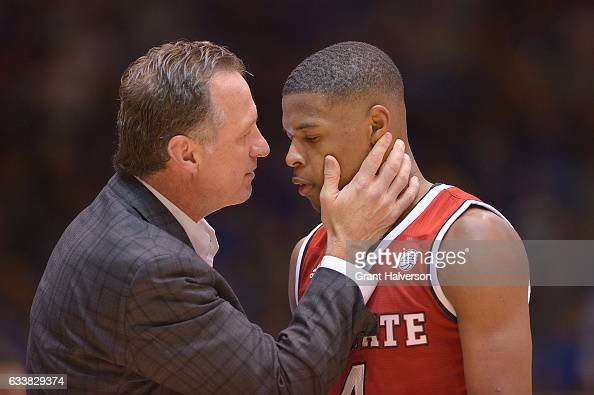 Head coach Mark Gottfried of the North Carolina State Wolfpack talks with Dennis Smith Jr #4 of the North Carolina State Wolfpack during their win...