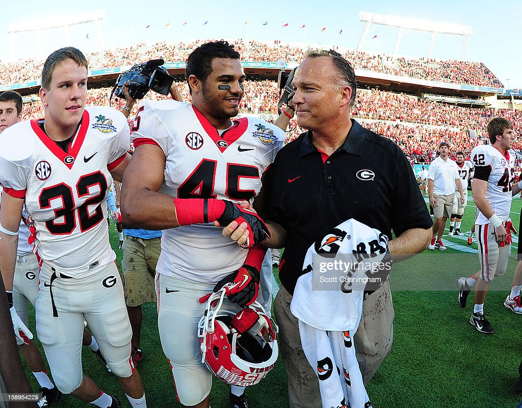 Head Coach Mark Richt of the Georgia Bulldogs celebrates with Christian Robinson #45 after the Capital One Bowl against the Nebraska Cornhuskers at the Citrus Bowl on January 1, 2013 in Orlando, Florida.