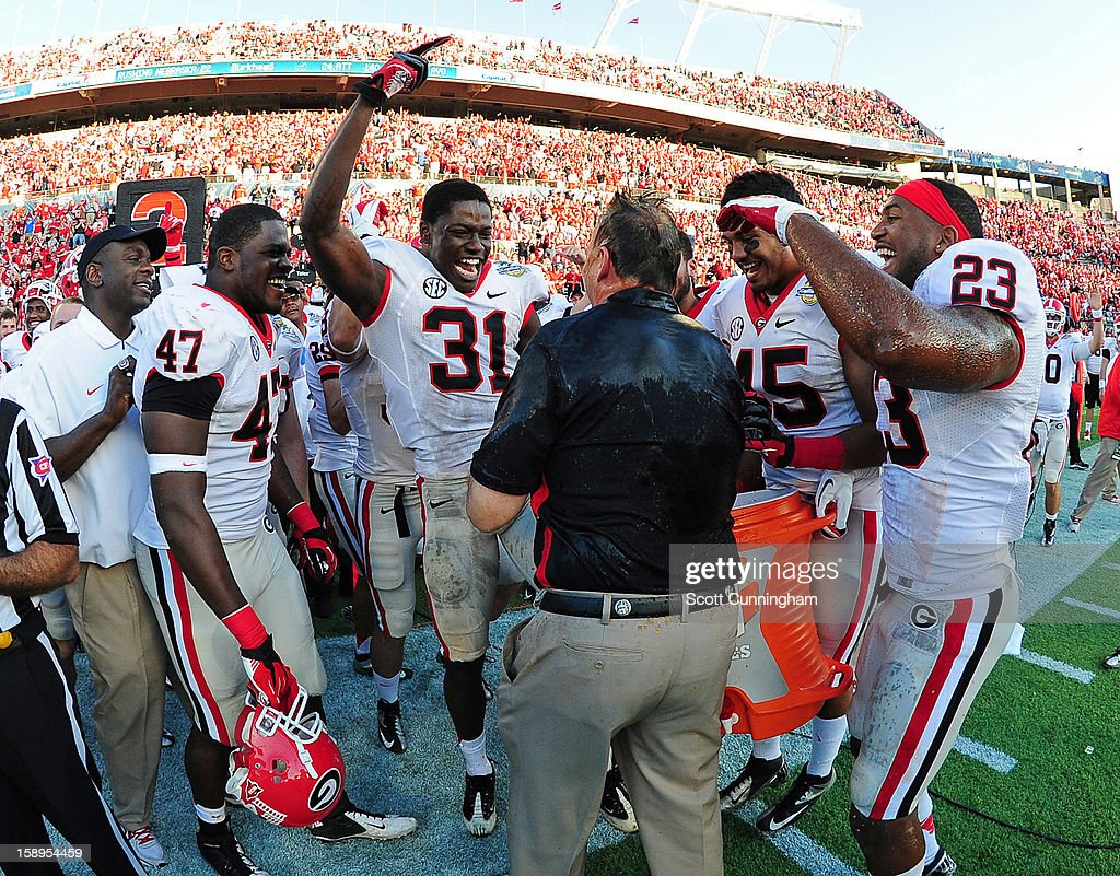 Head Coach Mark Richt of the Georgia Bulldogs celebrates with Ray Drew #47, Chris Conley #31, Christian Robinson #45, and Marc Deas #23 after being doused with Gatorade after the Capital One Bowl against the Nebraska Cornhuskers at the Citrus Bowl on January 1, 2013 in Orlando, Florida.