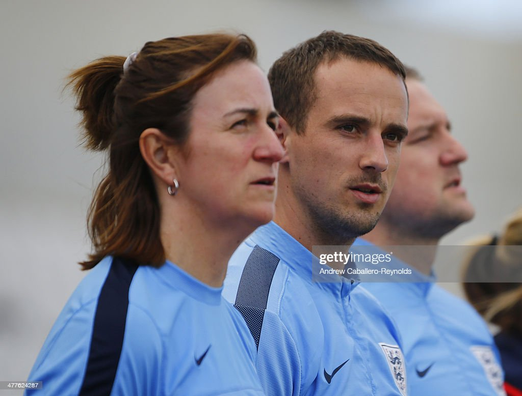 Head Coach Mark Sampson (C), Assistant coach Marieanne Spacey, and Goalkeeper coach Lee Kendal of England sing the national anthem before the Cyprus Cup match between England and Canada at GSP stadium on March 10, 2014 in Nicosia, Cyprus.