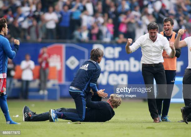 head coach Markus Gisdol assistant coach Frank Froehling and sports director Jens Todt celebrate after the Bundesliga match between Hamburger SV and...