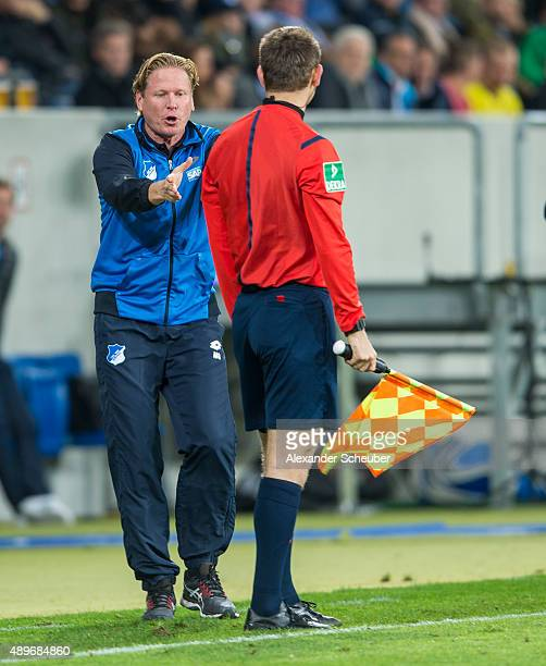 Head coach Markus Gisdol touches the referee during the bundesliga match between 1899 Hoffenheim and Borussia Dortmund at Wirsol RheinNeckarArena on...