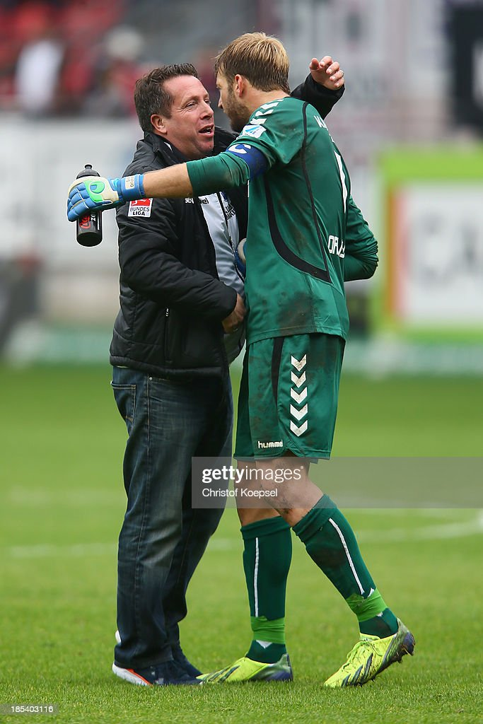 Head coach Markus Kauczinski of Karlsruhe embraces Dirk Orlishausen of Karlsruhe after the the Second Bundesliga match between 1. FC Kaiserslautern and Karlsruher SC at Fritz-Walter-Stadion on October 20, 2013 in Kaiserslautern, Germany. The match between Kaiserslautern and Karlsruhe ended 2-2.
