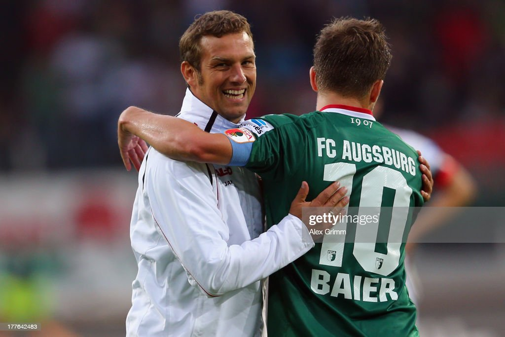 Head coach <a gi-track='captionPersonalityLinkClicked' href=/galleries/search?phrase=Markus+Weinzierl&family=editorial&specificpeople=5848121 ng-click='$event.stopPropagation()'>Markus Weinzierl</a> of Augsburg hugs <a gi-track='captionPersonalityLinkClicked' href=/galleries/search?phrase=Daniel+Baier&family=editorial&specificpeople=706624 ng-click='$event.stopPropagation()'>Daniel Baier</a> after the Bundesliga match between FC Augsburg and VfB Stuttgart at SGL Arena on August 25, 2013 in Augsburg, Germany.