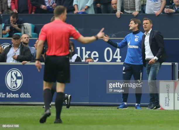 Head coach Markus Weinzierl of Schalke discusses with the assistant referee during the Bundesliga match between FC Schalke 04 and Borussia Dortmund...