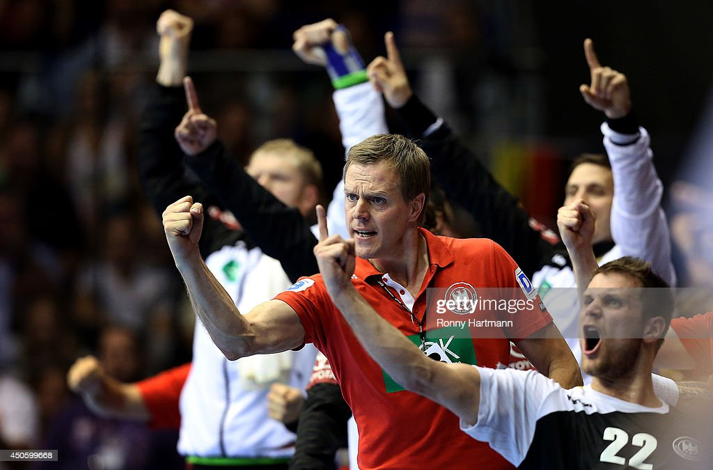 Head coach <a gi-track='captionPersonalityLinkClicked' href=/galleries/search?phrase=Martin+Heuberger&family=editorial&specificpeople=2084797 ng-click='$event.stopPropagation()'>Martin Heuberger</a> (C) of Germany celebrates during the IHF World Championship 2015 Playoff Leg Two between Germany and Poland at Getec-Arena on June 14, 2014 in Magdeburg, Germany.