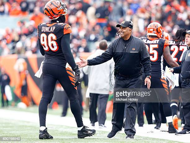 Head Coach Marvin Lewis of the Cincinnati Bengals congratualtes Carlos Dunlap of the Cincinnati Bengals after making a defensive stop during the...