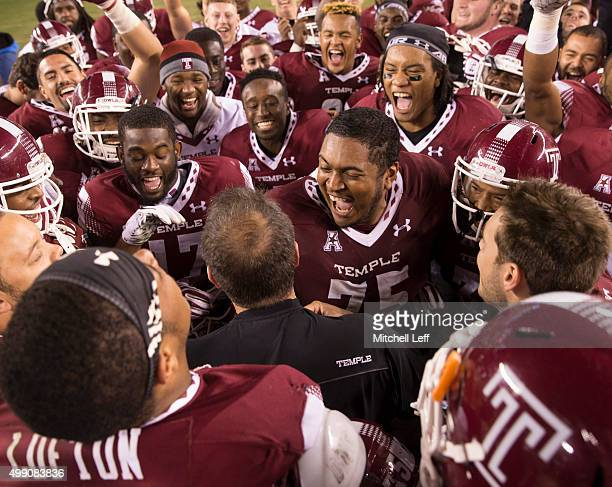 Head coach Matt Rhule of the Temple Owls celebrates winning the American Conference East Division with Shahbaz Ahmed and the rest of the team after...