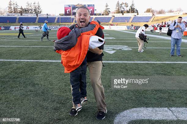 Head coach Matt Rhule of the Temple Owls gets a hug from a young fan following the Owls 3410 win over the Navy Midshipmen during the AAC Championship...