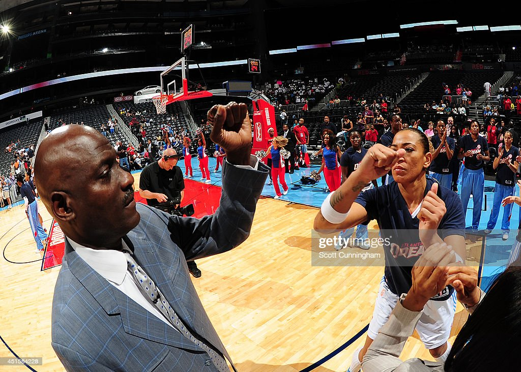 Head Coach Michael Cooper of the Atlanta Dream greets Erika deSouza #14 before the game against the Indiana Fever on July 1, 2014 at Philips Arena in Atlanta, Georgia.