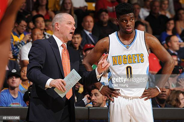 Head coach Michael Malone of the Denver Nuggets speaks with Emmanuel Mudiay of the Denver Nuggets during a preseason game against the Chicago Bulls...