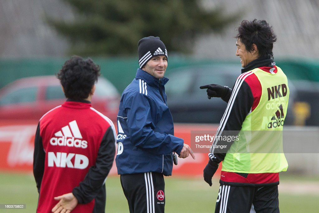 Head coach Michael Wiesinger speaks via interpreter Junpei Yamamori (L) with new player Mu Kanazaki (R) of 1 FC Nuernberg during a training session on January 30, 2013 at the Sportpark Valznerweiher in Nuremberg, Germany.