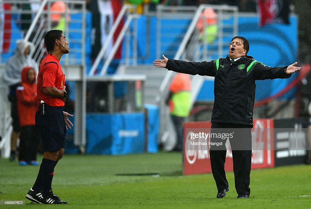 Head coach Miguel Herrera of Mexico reacts toward fourth official Norbert Hauata during the 2014 FIFA World Cup Brazil Group A match between Mexico and Cameroon at Estadio das Dunas on June 13, 2014 in Natal, Brazil.