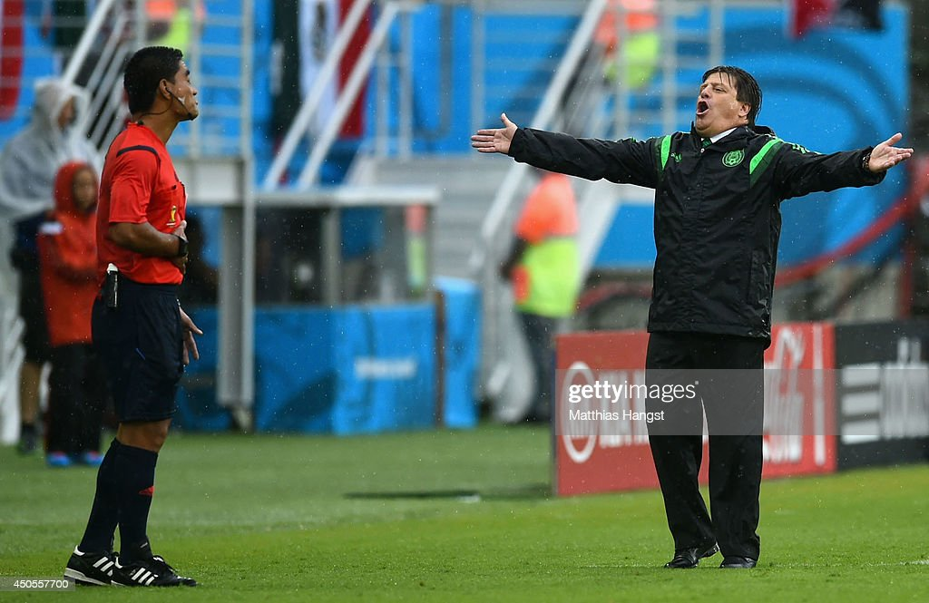 Head coach <a gi-track='captionPersonalityLinkClicked' href=/galleries/search?phrase=Miguel+Herrera+-+Entrenador+de+f%C3%BAtbol&family=editorial&specificpeople=12319687 ng-click='$event.stopPropagation()'>Miguel Herrera</a> of Mexico reacts toward fourth official <a gi-track='captionPersonalityLinkClicked' href=/galleries/search?phrase=Norbert+Hauata&family=editorial&specificpeople=7896620 ng-click='$event.stopPropagation()'>Norbert Hauata</a> during the 2014 FIFA World Cup Brazil Group A match between Mexico and Cameroon at Estadio das Dunas on June 13, 2014 in Natal, Brazil.