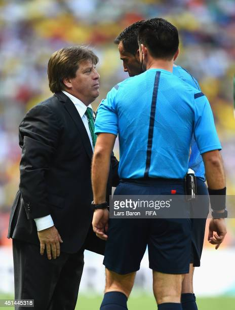Head coach Miguel Herrera of Mexico speaks with Referee Pedro Proenca during the 2014 FIFA World Cup Brazil Round of 16 match between Netherlands and...