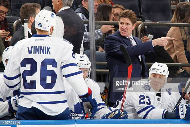 Head coach Mike Babcock of the Toronto Maple Leafs gives instructions to Daniel Winnik on the bench during the game against the New York Rangers at...